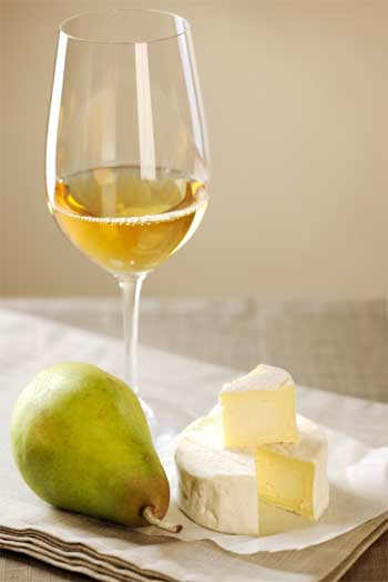 Camembert cheese, white wine  and pear; selective focus